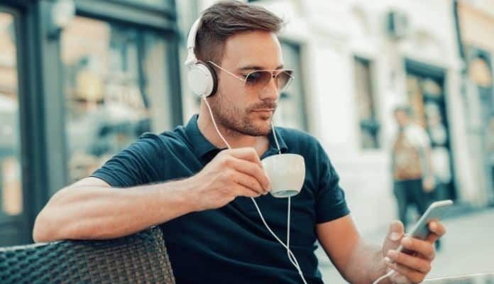 Man listening to music while having coffee brealk