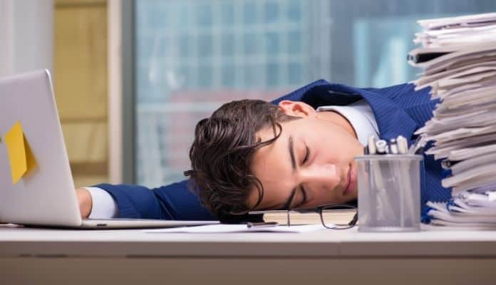 Overworked man sleeping while at work