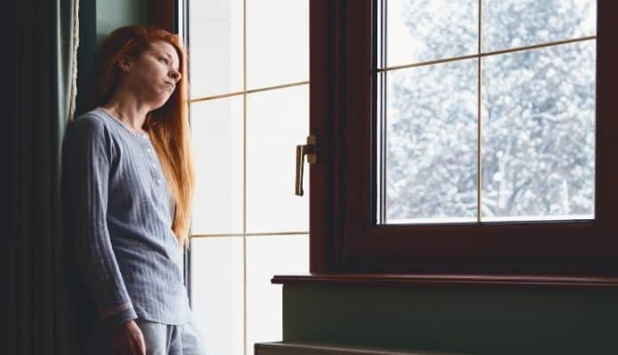 Woman with winter depression by window